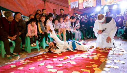 A man lies on a red carpet performing the traditional Chinese funeral wail