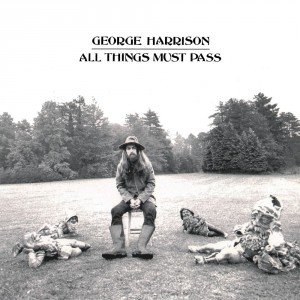 George Harrison sitting in a field with text in the sky that says all things must pass