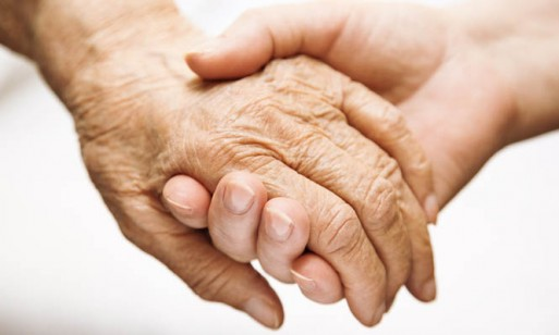 caregiver holding the hand of terminally ill patient
