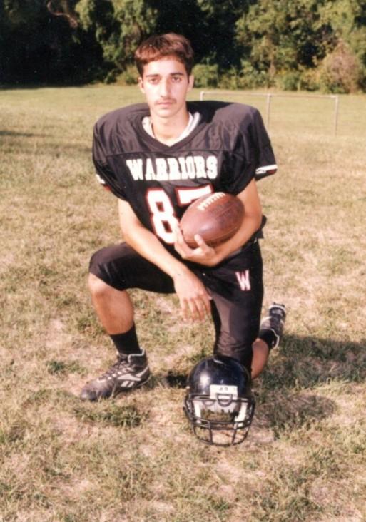 Adnan in high school holding a football and wearing a football uniform