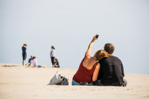 A couple taking a selfie with a phone on the beach