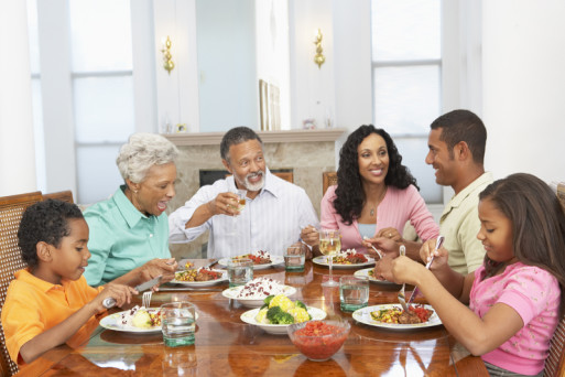 A multi-generational family smiles over supper table conversation about estate planning