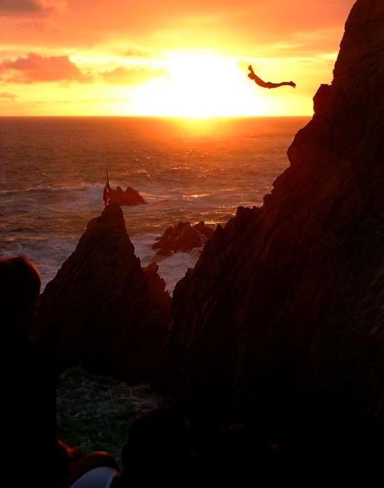 man cliff diving at sunset to live a wild life