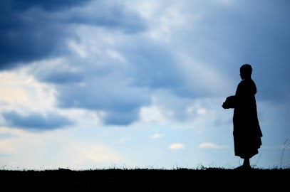 Buddhist monk looking at a cloudy sky