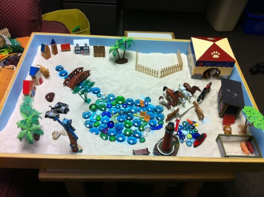 Sand tray therapy using symbolic objects