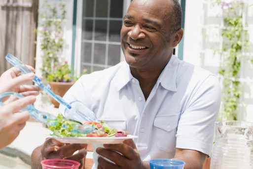 A fit African American middle aged man being served a healthy salad