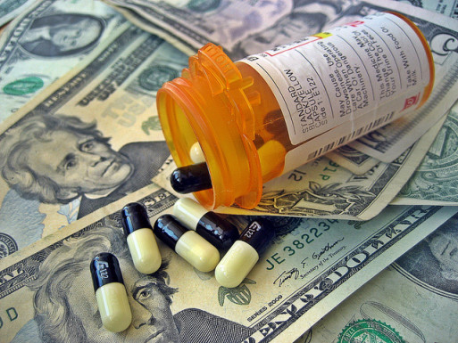 A bottle of pills spilling onto a stack of dollars represents soaring cost of medical care
