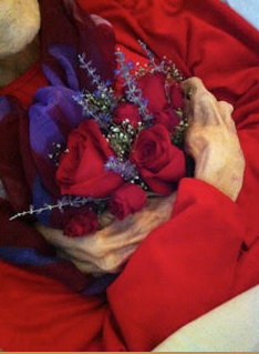 hands of a dead loved one holding flowers at a home funeral