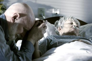 A man holds the hand of his dying wife