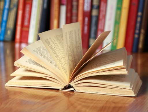 Open book lays on desk in front of bookshelf