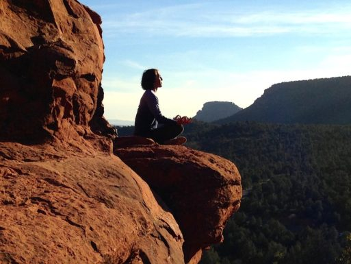 A woman meditates about life and death while she sits on a cliff ledge