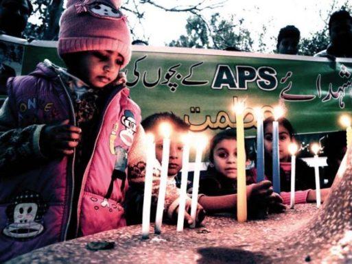 Children light candles at a memorial