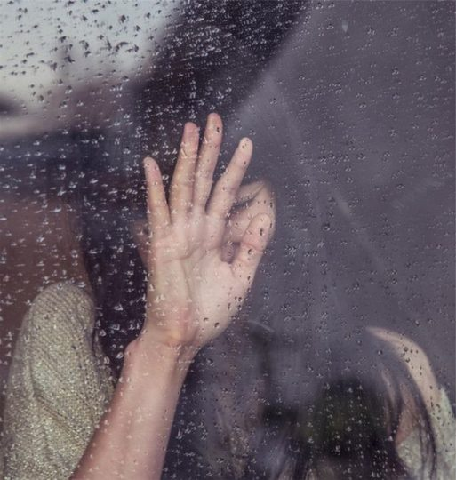 Grieving woman standing at a window in the rain