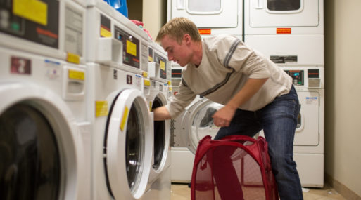 Young man doing laundry reminds us to use time wisely