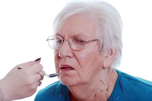 Elderly woman being fed from a spoon