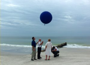 Family on a beach releasing a balloon containing loved one's cremains