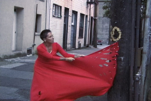 Rebecca Belmore tearing a red dress as an expression of grief in Vigil