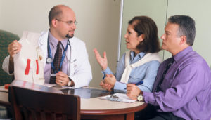 A doctor speaks with two patients about their medical intervention options