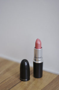 A tube of lipstick sitting on a table, similar to the photographs Ruibal used in her art about death and grief
