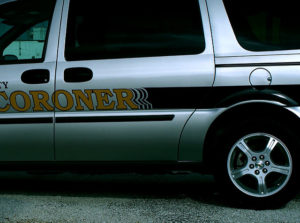 A coroner vehicle driving along the road