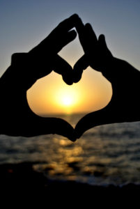 Heart hands at sunset speak of loss and love