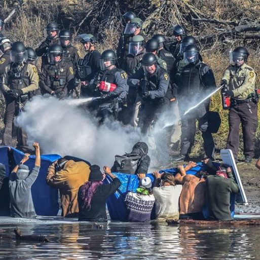 Police in full military gear spray tear gas and pepper spray on people protesting the Dakota Access Pipeline