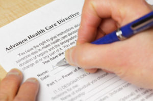 A person filling out a form titled Advance Directive and a pen.