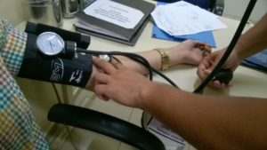 Healthcare worker taking a patients blood pressure to assess palliative care needs