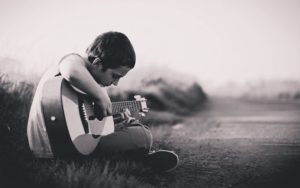 A young boy plays a guitar, to override the death rattle of someone who is dying