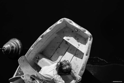 An image of a child looking into the water from a small boat symbolizes the mystery of death and dying