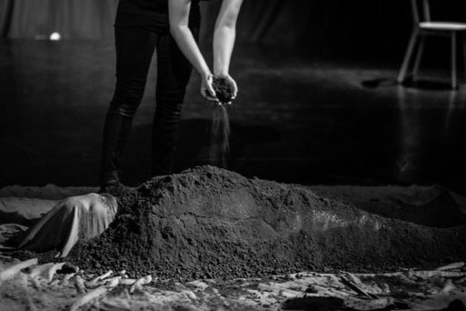 an image of a shrouded body being covered with dirt in death and dying exhibit