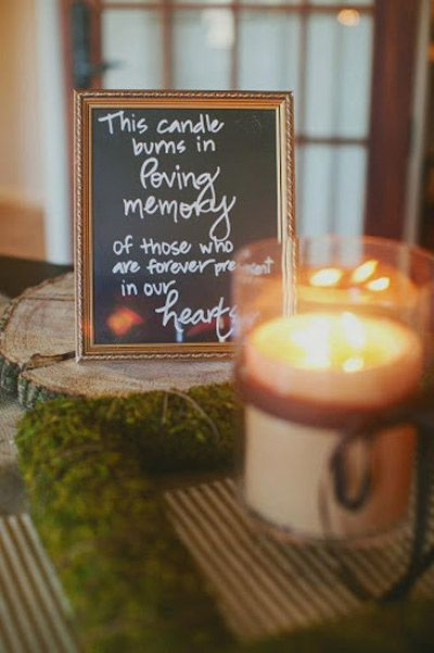 A candle next to a plaque commemorating a loved one is part of a memorial ceremony