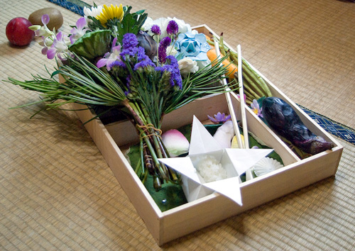 flowers and origami in a wooden box are part of a Japanese funeral ceremony