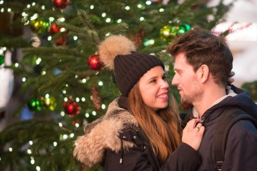 A couple smile at each other in front of a Christmas tree