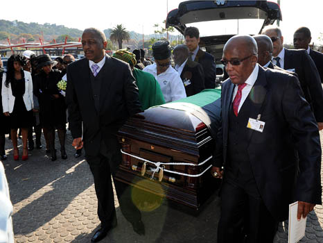Two men help carry a coffin out of a car in South Africa in a solemn ritual unlike after-tears parties
