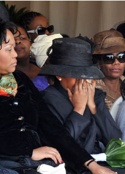 A widow cries into her hands at her husband's funeral in South Africa