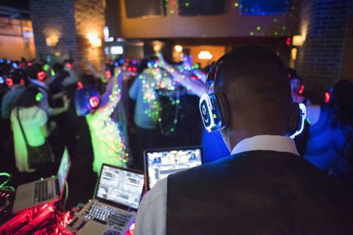 A DJ wearing headphones plays music for a crowd of young people at an after-tears party