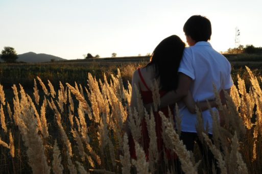 Couple with arms around eachother staring into sunset