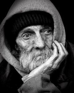 Homeless man with chin in palm