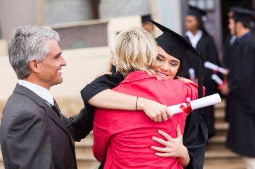Happy young woman hugging parents at graduation despite student loan dent