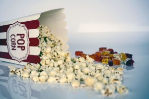Box of popcorn spilt next to candy to symbolize entertainment.
