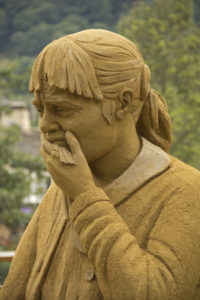 A sand sculpture of a grieving woman holding a tissue and looking like she is going to cry