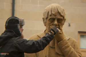An artist finishes sculpting the sand on the woman's face, which looks much older now, with more wrinkles