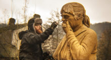 A Sand In Your Eye artist adds details to the sand sculpture's face, a grieving woman