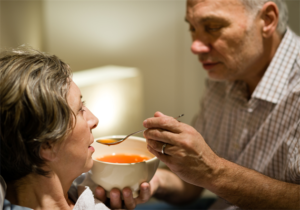 A man feeds his wife soup