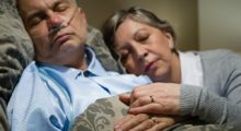 An exhausted caregiver sleeping next to her husband shows caregivers stress