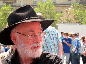 Terry Pratchett stands outside near a crowd of people, wearing his signature reading glasses and black fedora