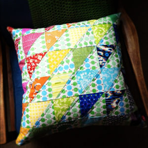 A homemade memory pillow with a detailed and colorful triangle pattern