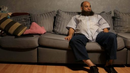 Mohamed Bzeek, who takes in foster children who are ill, sitting on living room couch