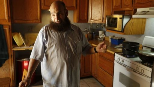 Mohamed Bzeek, who takes in sick foster children, standing in the kitchen
